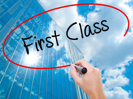 Man Hand writing First Class with black marker on visual screen. Business, technology, internet concept. Modern business skyscrapers background. Stock Photo