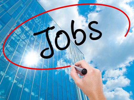 joblessness: Man Hand writing Jobs with black marker on visual screen. Business, technology, internet concept. Modern business skyscrapers background. Stock Image