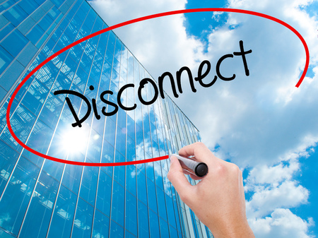 Man Hand writing Disconnect with black marker on visual screen. Business, technology, internet concept. Modern business skyscrapers background. Stock Photo
