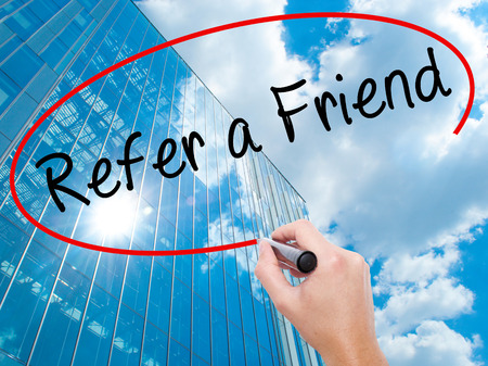 Man Hand writing Refer a Friend  with black marker on visual screen. Business, technology, internet concept. Modern business skyscrapers background. Stock Image