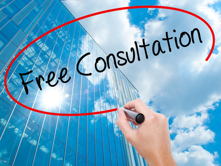 Man Hand writing Free Consultation with black marker on visual screen.  Business, technology, internet concept. Modern business skyscrapers background. Stock Photo Stock Photo