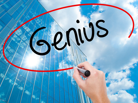 savant: Man Hand writing Genius  with black marker on visual screen.  Business, technology, internet concept. Modern business skyscrapers background. Stock Photo Stock Photo
