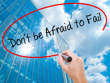 Man Hand writing Dont be Afraid to Fail with black marker on visual screen. Business, technology, internet concept. Modern business skyscrapers background. Stock Photo