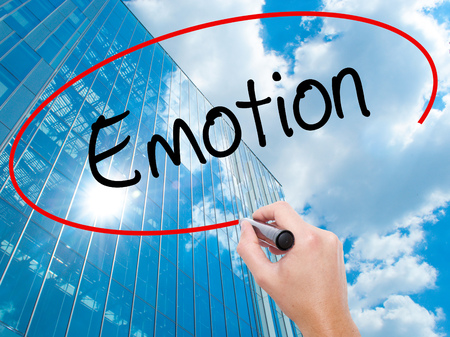 Man Hand writing Emotion with black marker on visual screen.  Business, technology, internet concept. Modern business skyscrapers background. Stock Photo