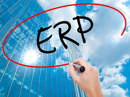 Man Hand writing  ERP (Enterprise Resource Planning)   with black marker on visual screen.  Business, technology, internet concept. Modern business skyscrapers background. Stock Photo Stock Photo