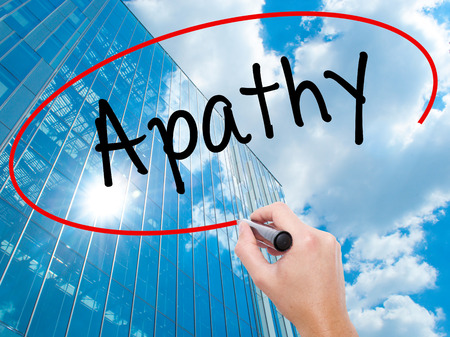 Man Hand writing Apathy  with black marker on visual screen.  Business, technology, internet concept. Modern business skyscrapers background. Stock Photo Stock Photo