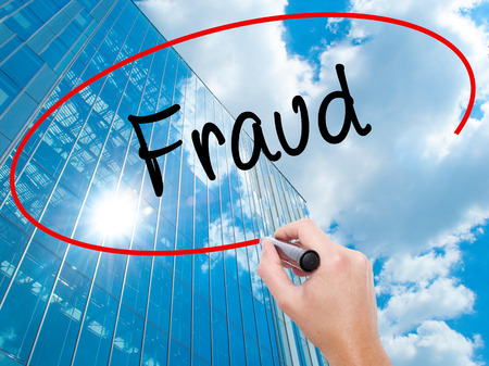 Man Hand writing Fraud with black marker on visual screen. Business, technology, internet concept. Modern business skyscrapers background. Stock Photo