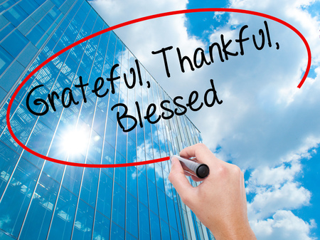 Man Hand writing  Grateful Thankful Blessed with black marker on visual screen.  Business, technology, internet concept. Modern business skyscrapers background. Stock Photo