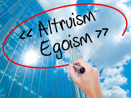 Man Hand writing Altruism - Egoism with black marker on visual screen.  Business, technology, internet concept. Modern business skyscrapers background. Stock Photo