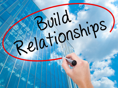 Man Hand writing Build Relationships with black marker on visual screen. Business, technology, internet concept. Modern business skyscrapers background. Stock Image