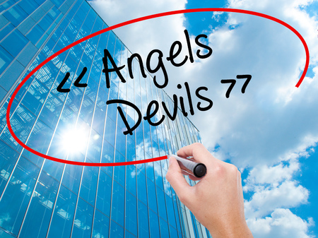 Man Hand writing Angels - Devils with black marker on visual screen.  Business, technology, internet concept. Modern business skyscrapers background. Stock Photo