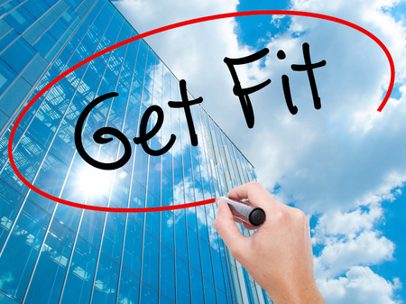 work less: Man Hand writing Get Fit  with black marker on visual screen.  Business, technology, internet concept. Modern business skyscrapers background. Stock Photo Stock Photo