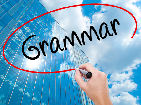 verb: Man Hand writing Grammar with black marker on visual screen.  Business, technology, internet concept. Modern business skyscrapers background. Stock Photo