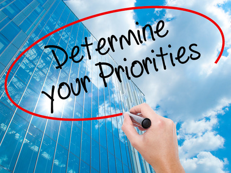 Man Hand writing Determine your Priorities with black marker on visual screen. Business, technology, internet concept. Modern business skyscrapers background. Stock Photo