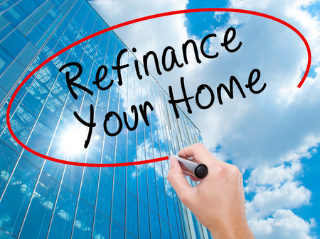 Man Hand writing Refinance Your Home with black marker on visual screen. Business, technology, internet concept. Modern business skyscrapers background. Stock Image