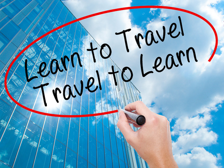 positiveness: Man Hand writing Learn to Travel. Travel to Learn with black marker on visual screen. Travel, technology, internet concept. Modern business skyscrapers background. Stock Image