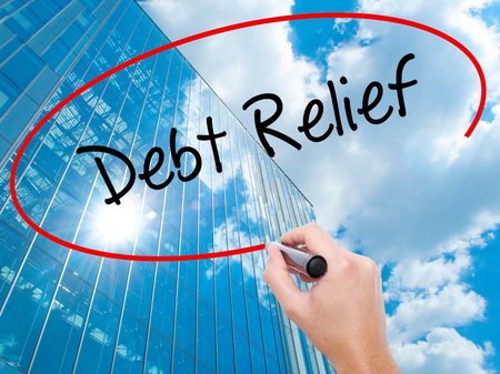 trouble free: Man Hand writing Debt Relief with black marker on visual screen. Business, technology, internet concept. Modern business skyscrapers background. Stock Photo