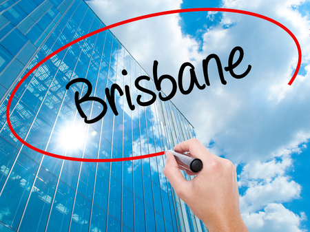Man Hand writing Brisbane  with black marker on visual screen. Business, technology, internet concept. Modern business skyscrapers background. Stock Photo Stock Photo
