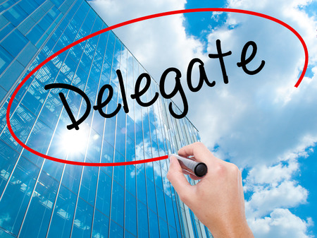 delegar: Man Hand writing Delegate with black marker on visual screen. Business, technology, internet concept. Modern business skyscrapers background. Stock Photo