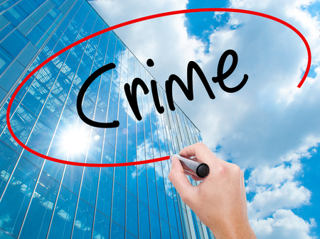 animal private: Man Hand writing Crime with black marker on visual screen.  Business, technology, internet concept. Modern business skyscrapers background. Stock Photo