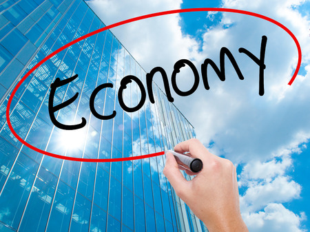 Man Hand writing Economy with black marker on visual screen.  Business, technology, internet concept. Modern business skyscrapers background. Stock Photo Stock Photo