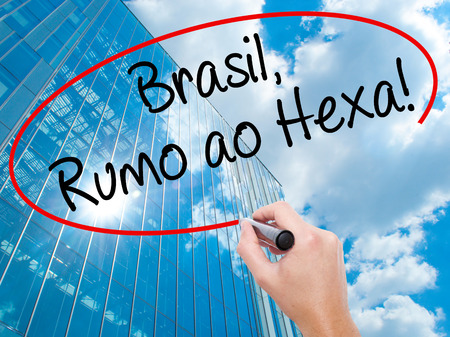 Man Hand writing Brasil, Rumo ao Hexa! with black marker on visual screen.  Business, technology, internet concept. Modern business skyscrapers background. Stock Photo Stock Photo
