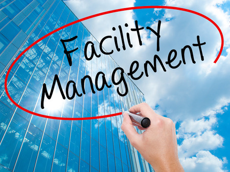 Man Hand writing Facility Management with black marker on visual screen. Business, technology, internet concept. Modern business skyscrapers background. Stock Photo