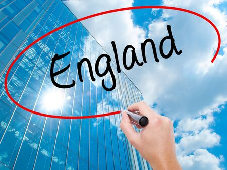 premier: Man Hand writing England with black marker on visual screen. Business, technology, internet concept. Modern business skyscrapers background. Stock Photo Stock Photo