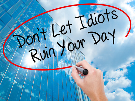 stupidity: Man Hand writing Dont Let Idiots Ruin Your Day with black marker on visual screen. Business, technology, internet concept. Modern business skyscrapers background. Stock Photo