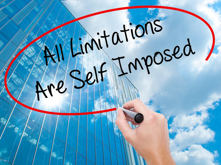 imposed: Man Hand writing All Limitations Are Self Imposed with black marker on visual screen.  Business, technology, internet concept. Modern business skyscrapers background. Stock Photo