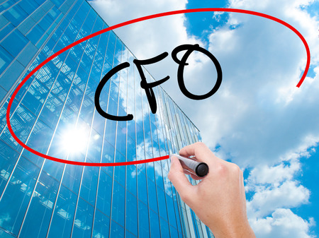 comité d entreprise: Man Hand writing CFO (Chief Financial Officer) with black marker on visual screen.  Business, technology, internet concept. Modern business skyscrapers background. Stock Photo Banque d'images