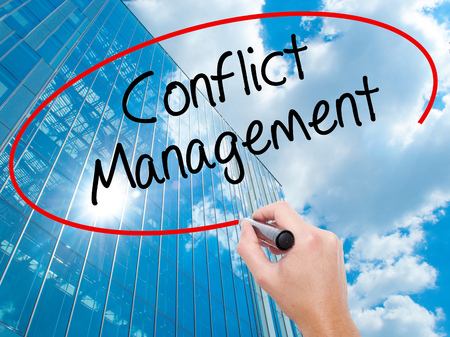 Man Hand writing Conflict Management with black marker on visual screen.  Business, technology, internet concept. Modern business skyscrapers background. Stock Photo