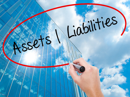 Man Hand writing Assets Liabilities with black marker on visual screen. Business, technology, internet concept. Modern business skyscrapers background. Stock Photo