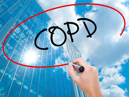 Man Hand writing COPD with black marker on visual screen. Business, technology, internet concept. Modern business skyscrapers background. Stock Photo Stock Photo