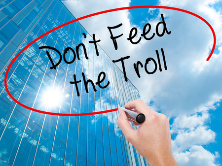 instigator: Man Hand writing Dont Feed the Troll with black marker on visual screen.  Business, technology, internet concept. Modern business skyscrapers background. Stock Photo
