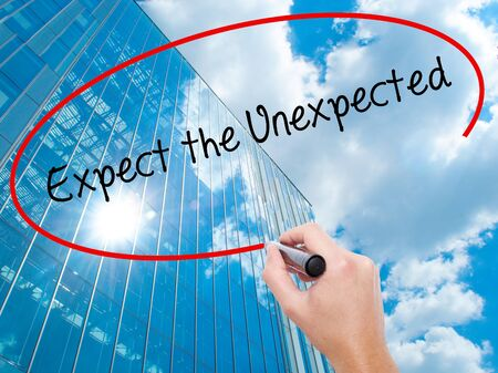 unexpected: Man Hand writing Expect the Unexpected with black marker on visual screen. Business, technology, internet concept.