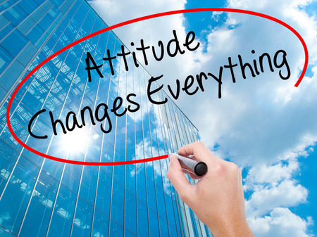 Man Hand writing Attitude Changes Everything with black marker on visual screen.  Business, technology, internet concept. Modern business skyscrapers background. Stock Photo