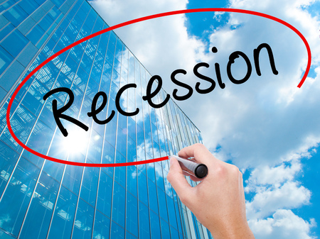 Man Hand writing Recession with black marker on visual screen. Business, technology, internet concept. Modern business skyscrapers background. Stock Image Stock Photo