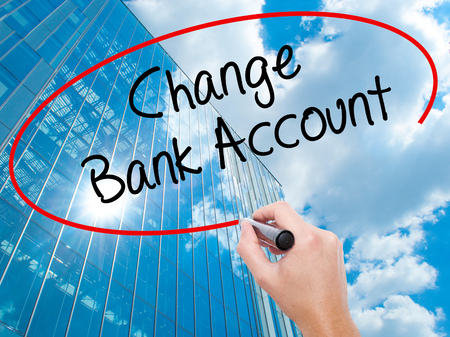 Man Hand writing Change Bank Account with black marker on visual screen.  Business, technology, internet concept. Modern business skyscrapers background. Stock Photo