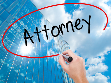 patents: Man Hand writing Attorney  with black marker on visual screen. Business, technology, internet concept. Modern business skyscrapers background. Stock Photo Stock Photo