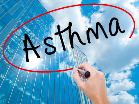 Man Hand writing Asthma with black marker on visual screen. Business, technology, internet concept. Modern business skyscrapers background. Stock Image Stock Photo