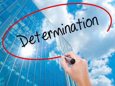 Man Hand writing Determination  with black marker on visual screen. Business, technology, internet concept. Modern business skyscrapers background. Stock Photo