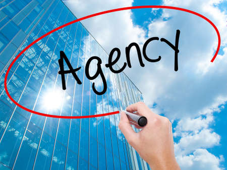 Man Hand writing Agency with black marker on visual screen. Business, technology, internet concept. Modern business skyscrapers background. Stock Photo Stock Photo