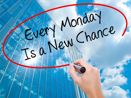another way: Man Hand writing Every Monday Is a New Chance with black marker on visual screen. Business, technology, internet concept. Modern business skyscrapers background. Stock Photo