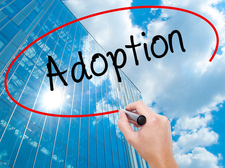 daughter in law: Man Hand writing Adoption with black marker on visual screen. Business, technology, internet concept. Stock Photo