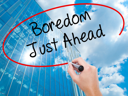 Man Hand writing Boredom Just Ahead with black marker on visual screen.  Business, technology, internet concept. Modern business skyscrapers background. Stock Photo