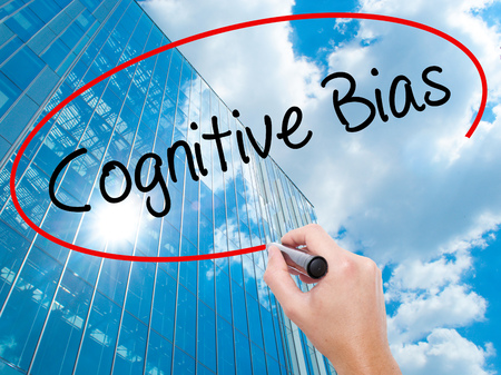 Man Hand writing Cognitive Bias with black marker on visual screen.  Business, technology, internet concept. Modern business skyscrapers background. Stock Photo Stock Photo