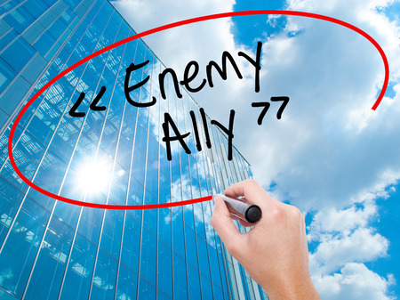 Man Hand writing Enemy - Ally with black marker on visual screen.  Business, technology, internet concept. Modern business skyscrapers background. Stock Photo Stock Photo