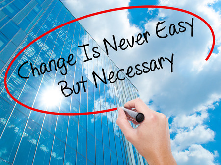 Man Hand writing Change Is Never Easy But Necessary with black marker on visual screen.  Business, technology, internet concept. Modern business skyscrapers background. Stock Photo Stock Photo