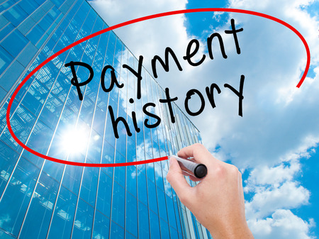 Man Hand writing Payment history with black marker on visual screen. Business, technology, internet concept. Modern business skyscrapers background. Stock Image Stock Photo